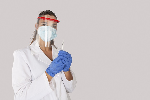 surgeon with face mask and plastic shield